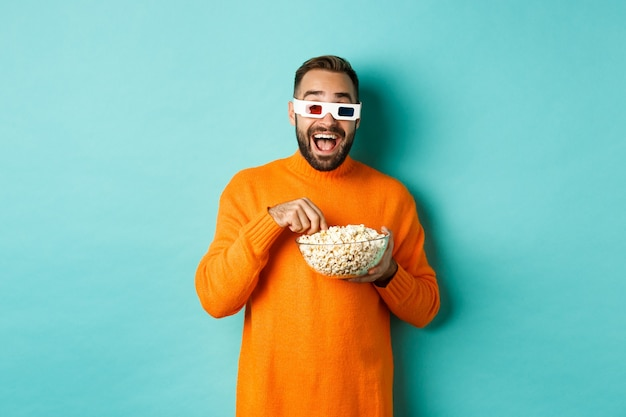 Happy and amazed young man in 3d glasses watching comedy movie, looking at tv screen and eating popcorn, standing over blue background.
