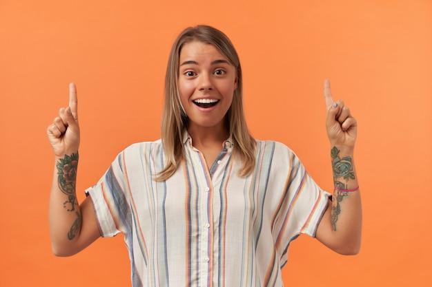 ストライプのシャツに立って、オレンジ色の壁に隔離された空のスペースで空を指している幸せな驚く若い女性