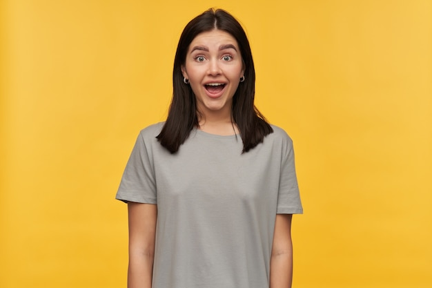 검은 머리와 회색 tshirt에 열린 입을 가진 행복 놀란 젊은 여자는 노란색 벽에 흥분 보인다