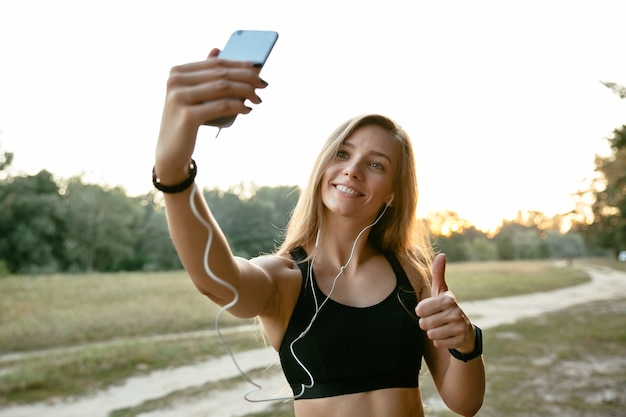 Happy amazing girl in headphones, takes a selfie on mobile phone, showing a thumb up