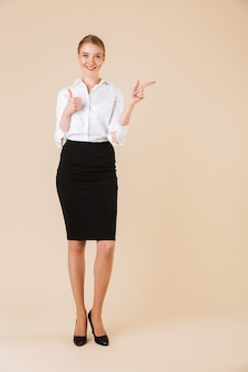 Happy amazing young business woman pointing showing thumbs up.