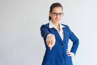 Happy ambitious young business lady pointing with finger and standing