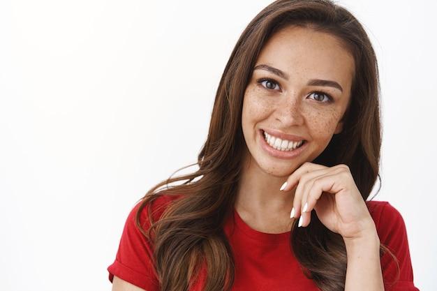 Felice giovane ragazza sciocca ambiziosa con le lentiggini in maglietta rossa, inclina la testa sorridendo gioiosamente toccando teneramente il mento, ridendo sensualmente all'appuntamento romantico, muro bianco