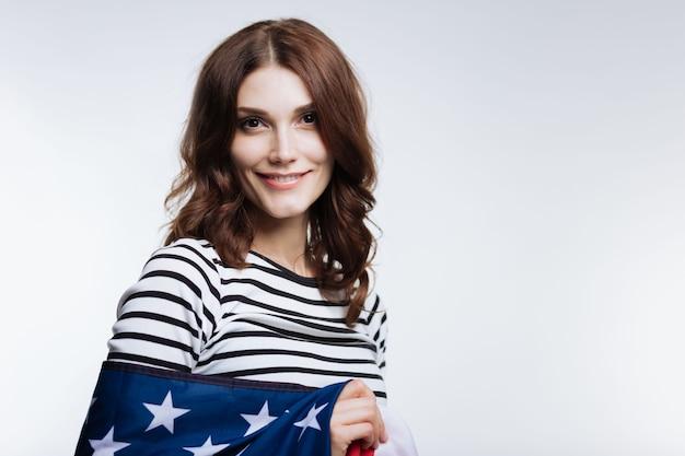 Счастливый американец. жизнерадостная рыжеволосая молодая женщина в полосатом пуловере улыбается, будучи завернутой в американский флаг