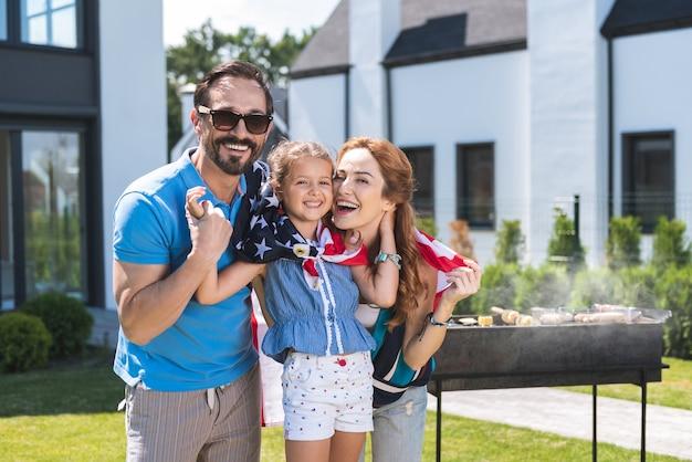 Счастливая американская семья с барбекю во время празднования дня независимости