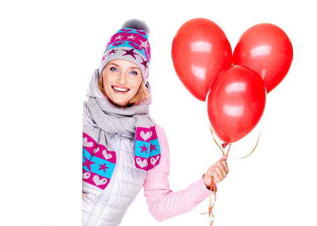 Happy american woman with red balloons looks from placard isolated on white