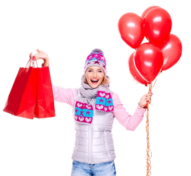 Happy american woman with red shopping bags and balloons isolated on white