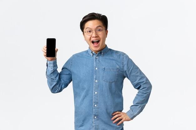 Felice e divertito bel ragazzo asiatico con bretelle e occhiali reagisce a fantastiche notizie, mostrando lo schermo del telefono cellulare, introducendo un'applicazione o un negozio, in piedi sfondo bianco stupito.
