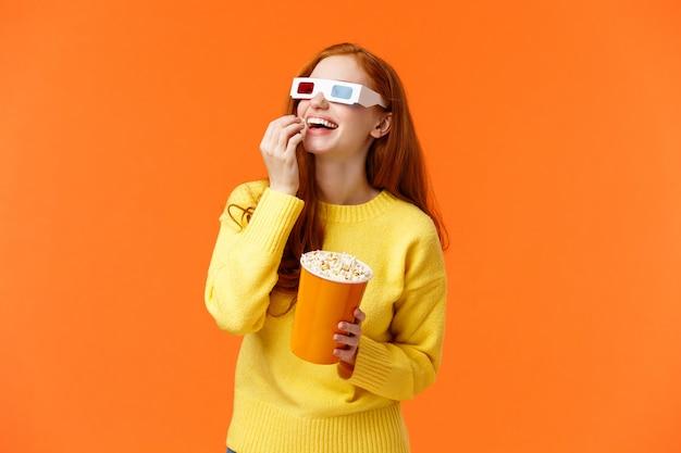 Веселая и веселая рыжая девушка любит смотреть фильмы в кинотеатрах, ходить в кино, есть попкорн и смотреть на экран