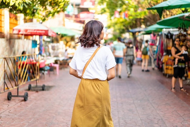 幸せで美しいアジアの女性がタイのカオサーンロードを旅行