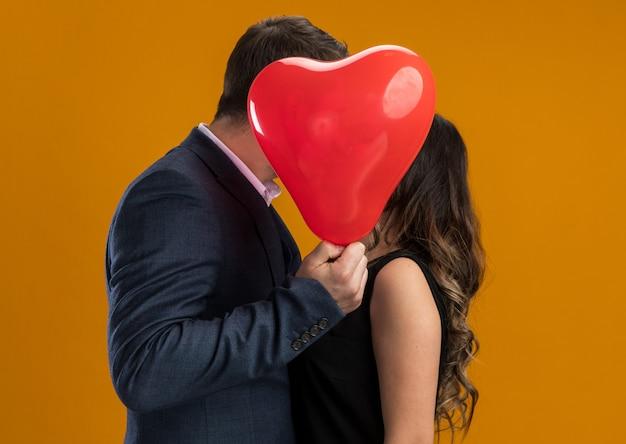 Счастливая и красивая пара, целующаяся за красным воздушным шаром в форме сердца, празднует день святого валентина