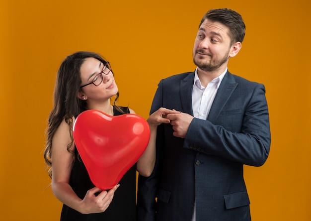 バレンタインデーを祝ってお互いを見てハートの形をした赤い風船を持つ幸せで美しいカップルの男性と女性