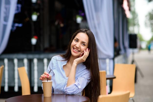 Счастливая и красивая девушка разговаривает по телефону и пьет кофе.