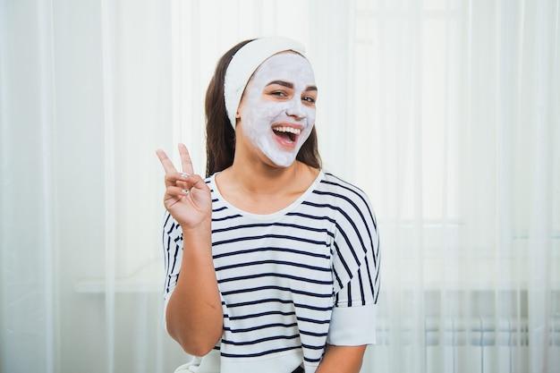그녀의 얼굴에 흰색 점토 마스크와 함께 행복하고 아름다운 소녀. 홈 뷰티 트리트먼트. 스킨 케어 및 회춘 개념.