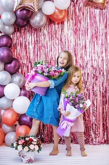 ピンクの写真ゾーンで一緒に休日に花を持つ幸せで美しい子供2人の女の子