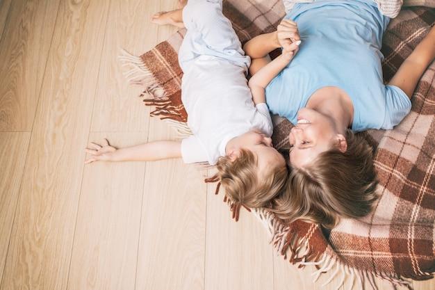 Счастливая и красивая семья матери и ребенка вместе дома лежит на одеяле на полу
