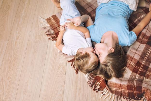 집에서 함께 행복하고 아름다운 어머니와 자식 가족은 바닥에 담요에 누워