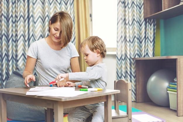 幸せで美しい母と子の家族が一緒に子供たちのテーブルに描画します