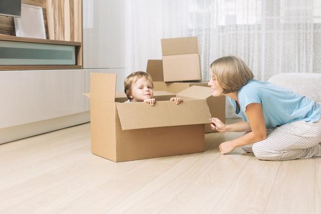 골판지 상자가 있는 새 집에서 행복하고 아름다운 엄마와 아이 가족