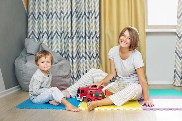 행복하고 아름다운 엄마와 아이 가족이 함께 보육원에서 장난감 자동차를 가지고 노는 모습
