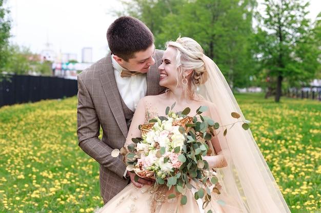 公園を歩いている幸せで美しい新婚夫婦。野外結婚式。