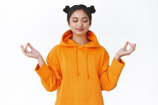 Счастливая и спокойная, расслабленная, улыбающаяся азиатская девушка, медитирующая в позе лотоса с жестом gen, закрывает глаза и мирно улыбается, чувствуя себя легко, с облегчением после тяжелого дня в университете