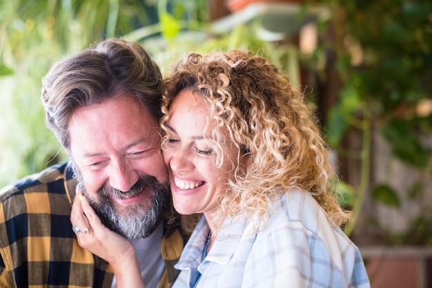 Счастливые и веселые взрослые кавказские пары портрета улыбаются и наслаждаются любовью и отношениями вместе - мужчина с бородой и женщина со светлыми длинными вьющимися волосами в чувстве нежности