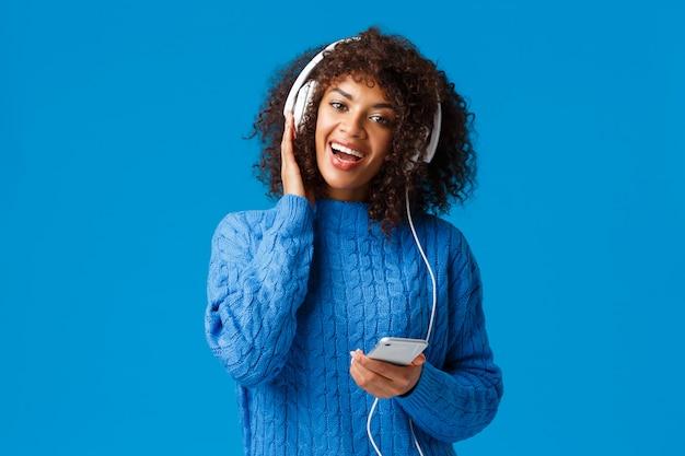 幸せで陽気なアフリカ系アメリカ人の女性がスマートフォンでカラオケゲームアプリをプレイし、歌と素晴らしい音楽、音質、青い背景に立ってヘッドフォンを着て