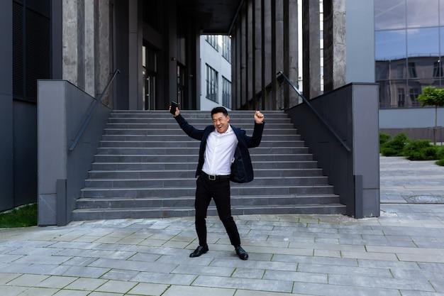 オフィスの近くで踊る幸せで陽気なアジアのビジネスマンは勝利と成功を喜ぶ