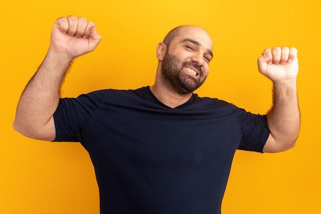 Счастливый и веселый бородатый мужчина в темно-синей футболке поднимает кулаки, как победитель, стоящий над оранжевой стеной