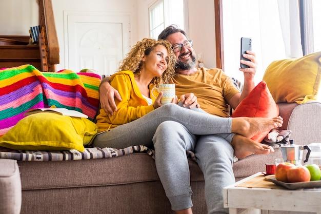 幸せで陽気な美しい大人の白人カップルが電話を使用してビデオ通話会議を行います