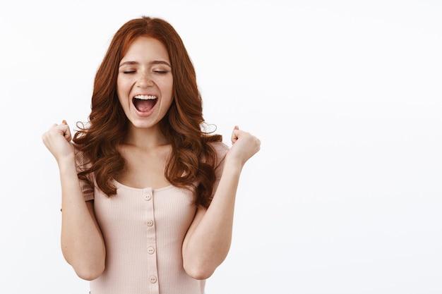 幸せで陽気なかわいい赤毛の女性の拳ポンプ、幸せと喜びから叫び、宝くじに勝ち、チャンピオンになり、白い壁に打ち勝つ