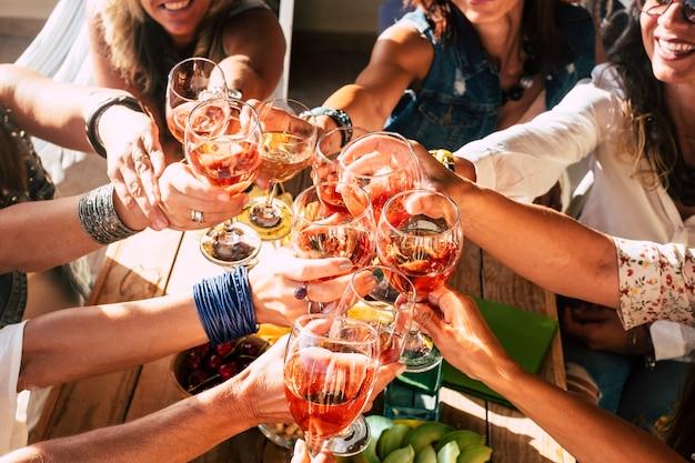 행복하고 쾌활한 사람들의 그룹 여성 젊은 친구가 함께 응원하고 레드 와인으로 축하 토스트
