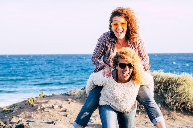 白人女性の幸せで陽気な中年カップルは、お互いを運び、たくさん笑って一緒に楽しんで遊んでいます