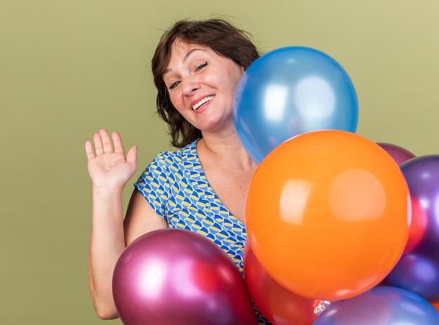 Счастливая и веселая женщина среднего возраста кучу разноцветных шаров, размахивая рукой, улыбаясь