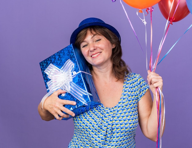 カラフルな風船の束を保持し、広く笑顔を提示するパーティーハットで幸せで陽気な中年女性