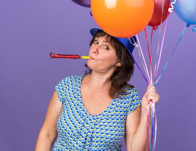 보라색 벽 위에 서 생일 파티를 축하 휘파람을 불고 다채로운 풍선의 무리를 들고 파티 모자에 행복하고 쾌활한 중년 여성