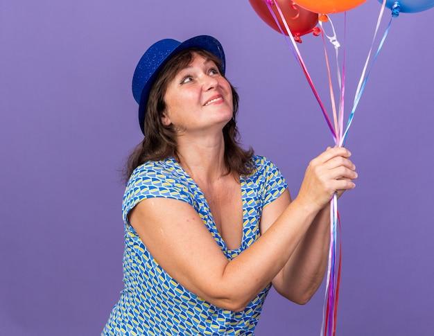 보라색 벽 위에 서 생일 파티를 광범위하게 축하 웃고 그들을보고 다채로운 풍선의 무리를 들고 파티 모자에 행복하고 쾌활한 중년 여성