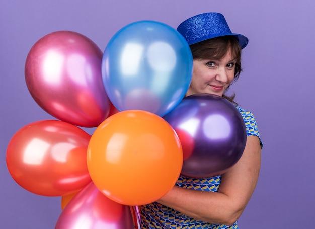 보라색 벽 위에 서 축하 생일 파티 미소 다채로운 풍선의 무리를 들고 파티 모자에 행복하고 쾌활한 중년 여자