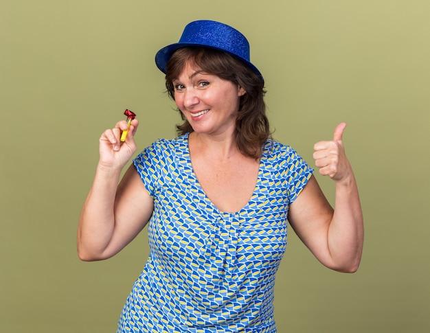 Счастливая и веселая женщина среднего возраста в партийной шляпе, держащая свисток, улыбаясь, показывает палец вверх