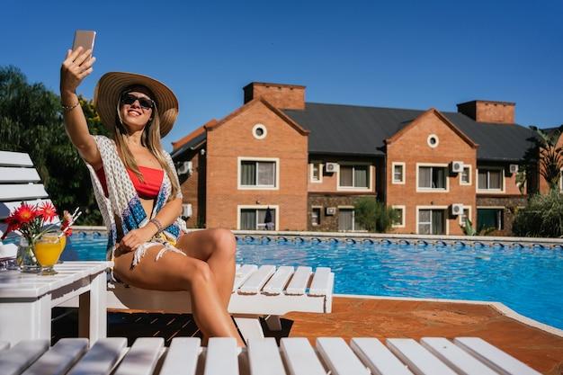 Счастливая и жизнерадостная женщина сидит на шезлонге у бассейна и делает селфи на свой мобильный телефон.