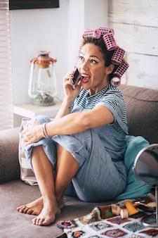 ソファに座って、友達と携帯電話で話している自宅で幸せで陽気な若い美しい女性-夜のパーティーの前にコンセプトを準備するための彼の髪のカーラー