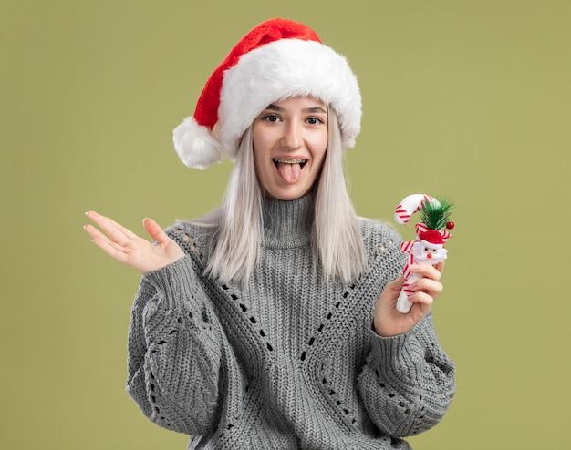 녹색 벽 위에 서 혀를 튀어 나와 크리스마스 사탕 지팡이를 들고 겨울 스웨터와 산타 모자에 행복하고 쾌활한 젊은 금발의 여자