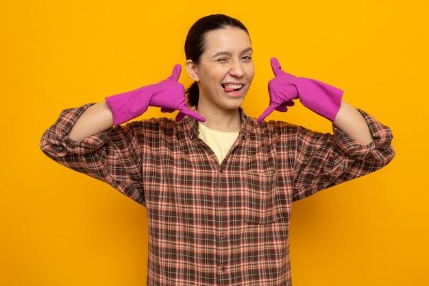 幸せで陽気な若い掃除をしている女性は、ゴム手袋をはめてカジュアルな服を着て、私をジェスチャーと呼んでいます