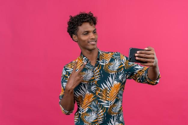 2本の指のジェスチャーを示す携帯電話でselfieを作る葉のプリントシャツに巻き毛を持つ幸せで陽気な若いハンサムな浅黒い肌の男