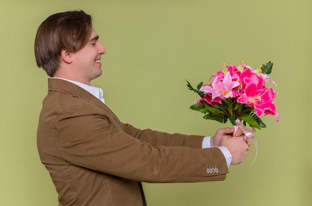 축하 할 꽃의 꽃다발을 들고 행복하고 쾌활한 젊은 남자