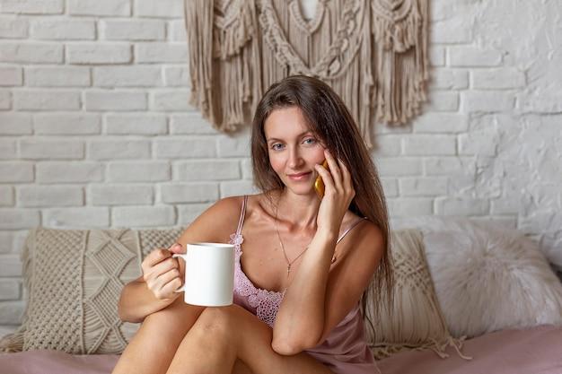 커피와 함께 침대에 앉아있는 동안 스마트 폰 복용 행복하고 쾌활한 젊은 여자.