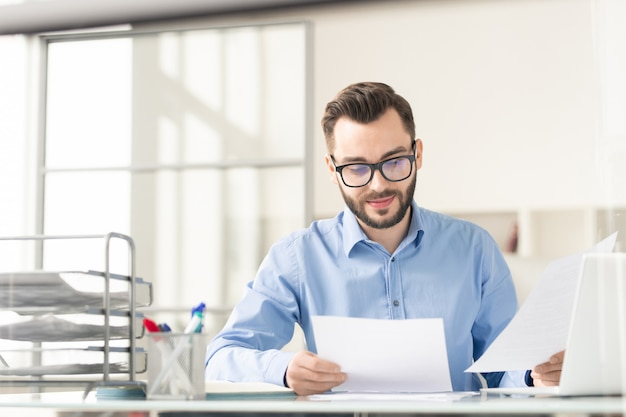 Счастливый и уверенный в себе бизнесмен с бумагами, готовящимися к отчету или прочтением условий контракта перед переговорами