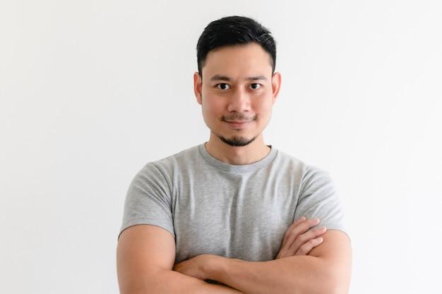 孤立した白い背景の上の灰色のtシャツで幸せで自信のある男