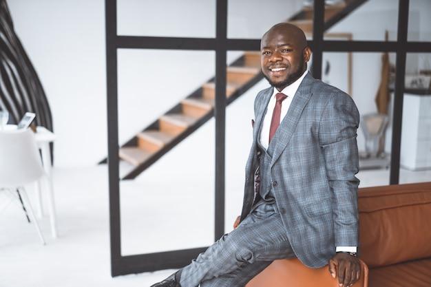 幸せで満足のいくビジネスマンアフリカ系アメリカ人の男が笑顔でロフトアパートのカメラを見て...